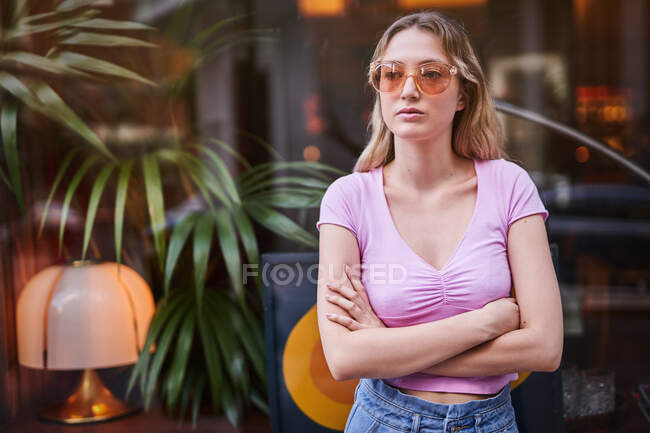Concerned female in sunglasses wearing casual clothes standing with crossed arms against glass wall in Madrid street — Stock Photo