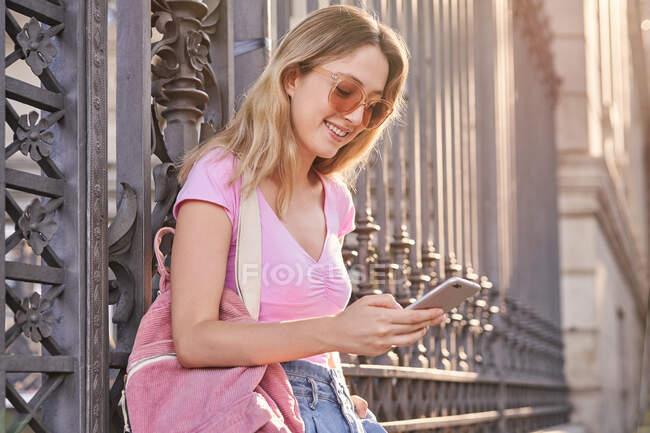 Vue latérale de la femelle positive avec sac à dos souriant tout en faisant défiler le téléphone mobile appuyé sur une clôture en métal — Photo de stock