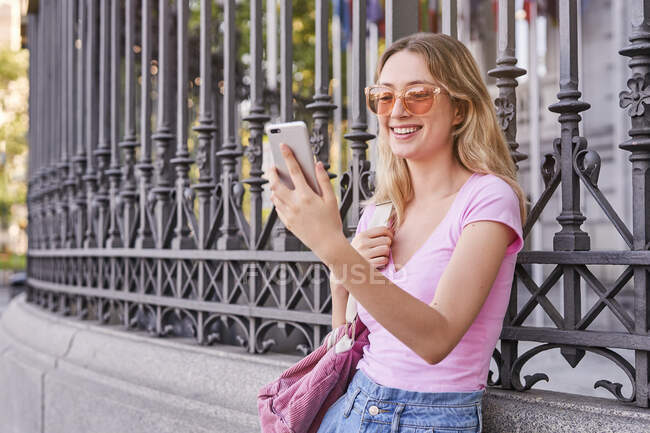 Side view of positive female with backpack smiling brightly while scrolling mobile phone leaning on metal fence — Stock Photo