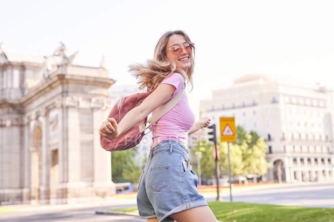 Felice femmina con in piedi sotto il sole durante il viaggio a Madrid — Foto stock