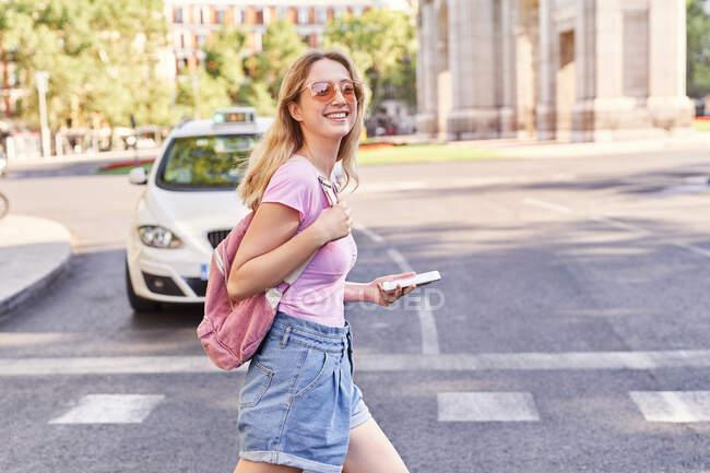 Vista laterale della giovane donna che cammina sull'attraversamento pedonale e controlla il percorso sul cellulare a Madrid — Foto stock