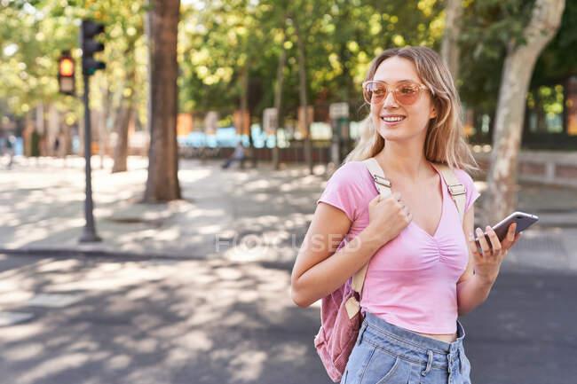 Giovane donna che cammina sull'attraversamento pedonale e controlla il percorso sul cellulare a Madrid — Foto stock