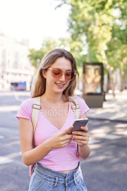Jeune femme marchant sur le passage piéton et vérifiant l'itinéraire sur téléphone portable à Madrid — Photo de stock
