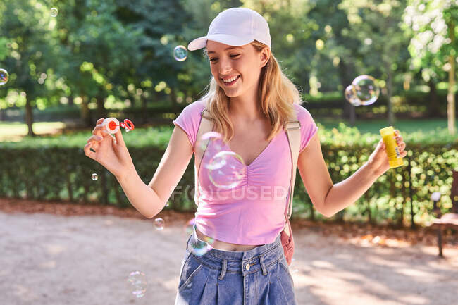 Carefree female blowing bubbles while spending sunny day in green park in Madrid — Stock Photo