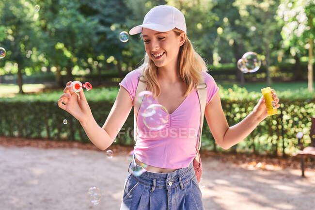 Обачна самка випускає бульбашки під час сонячного дня в зеленому парку в Мадриді. — стокове фото