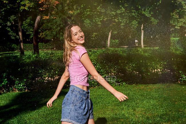 Mulher alegre em pé em salpicos no parque ensolarado — Fotografia de Stock