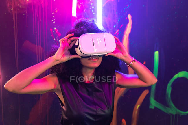 Shocked female wearing VR goggles touching air while experiencing cyberspace in studio with neon illumination — Stock Photo