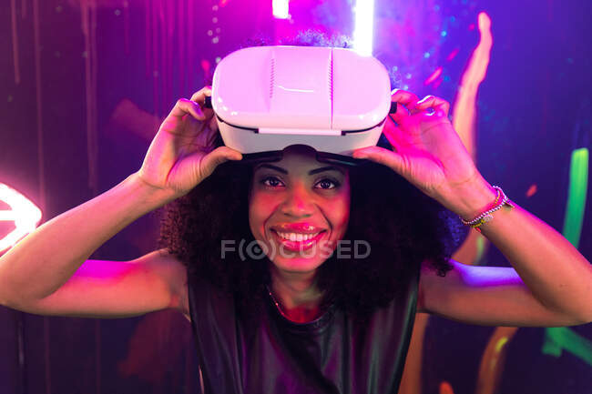 Positive African American female putting on VR goggles in room with glowing neon lights — Stock Photo