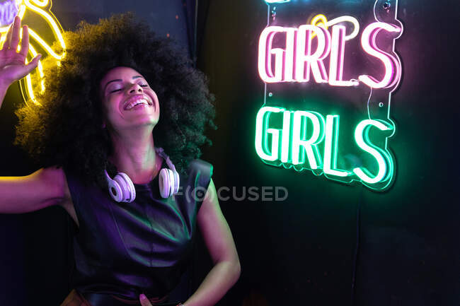 Smiling African American female with Afro hairstyle and wireless headphones on neck standing near bright neon signboard — Stock Photo