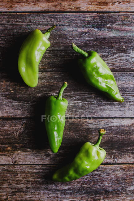 From above fresh green peppers with various shapes on smooth lumber table in rustic kitchen — Stock Photo