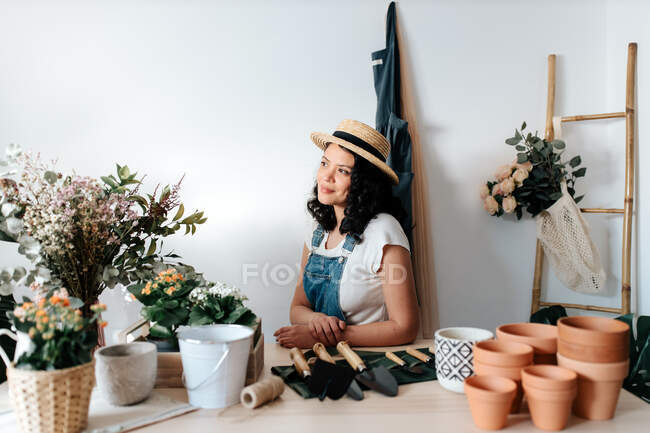 Young female horticulturist in straw hat sitting near flowers on table with assorted tools at home — Fotografia de Stock