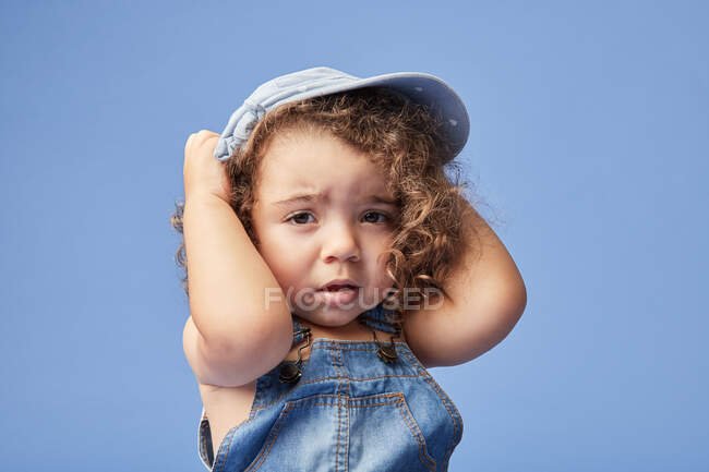 Adorable upset little kid with brown eyes wearing casual clothes and hat against blue background looking at camera — Stock Photo