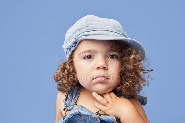 Adorabile bambino sconvolto con gli occhi marroni che indossa abiti casual e cappello sullo sfondo blu guardando altrove — Foto stock