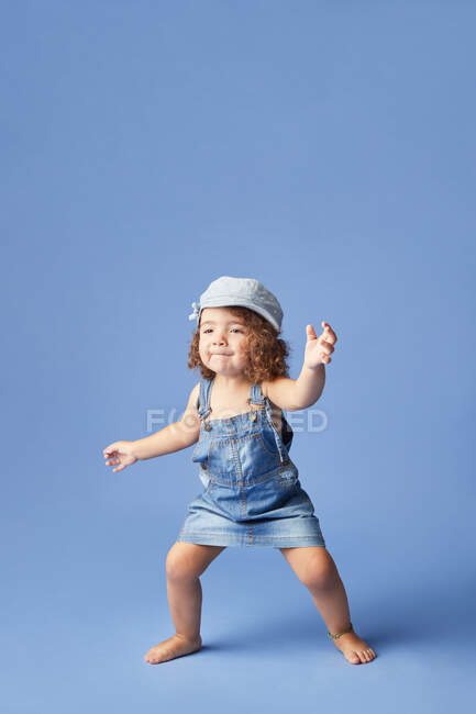 Charming barefoot child in denim dress and hat with curly hair looking away while dancing on blue background — Stock Photo