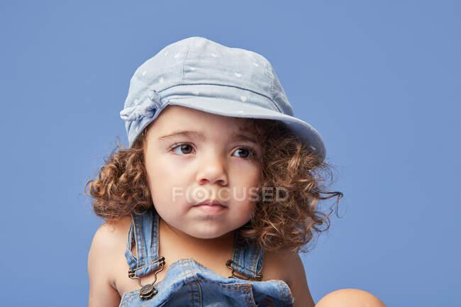 Приємна засмучена дитина з карими очима, одягнена в повсякденний одяг і капелюх на синьому фоні, дивлячись геть — стокове фото