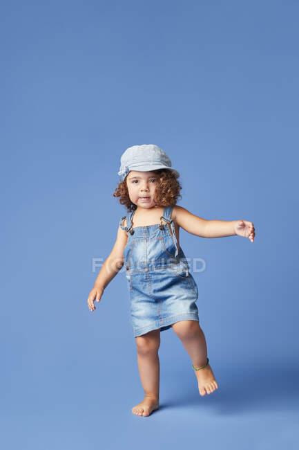 Criança descalça encantadora em vestido de ganga e chapéu com cabelo encaracolado olhando para longe enquanto dança no fundo azul — Fotografia de Stock