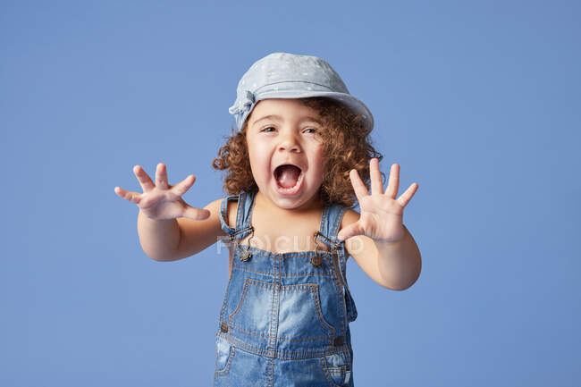 Charming barefoot child in denim dress and hat with curly hair looking a camera while standing on blue background making faces — Stock Photo