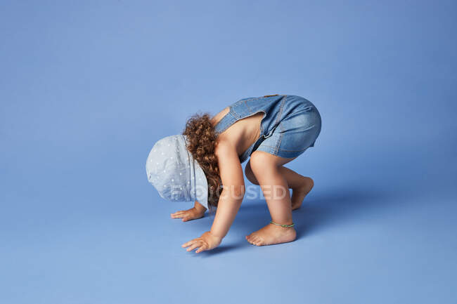 Side view full body of unrecognizable barefoot little girl standing upside down while playing in blue studio — Stock Photo