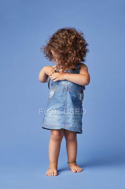 Criança descalça encantadora em vestido de ganga com cabelo encaracolado distraído com panos enquanto em pé sobre fundo azul — Fotografia de Stock