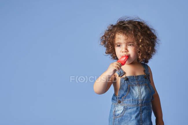 Poco emocional niña reflexiva de pie con paleta de fusión contra el fondo azul - foto de stock