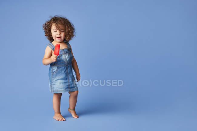 Cuerpo completo de niña encantada de pie con paleta de fusión sobre fondo azul - foto de stock