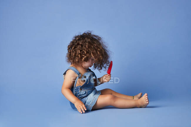 Full body side view of upset little girl on summer clothes barefooted sitting with ice cream against studio blue background — Stock Photo