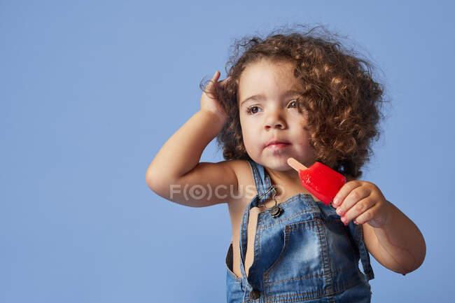 Sconvolto bambina guardando lontano in piedi con il gelato contro lo studio sfondo blu — Foto stock