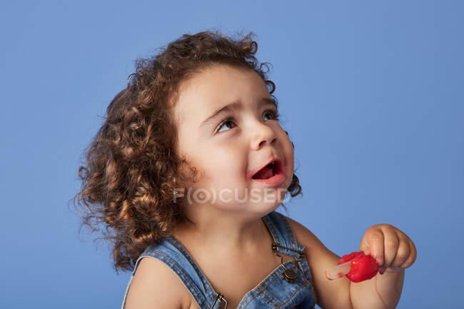 Petite fille bouleversée regardant debout avec de la crème glacée sur fond bleu studio — Photo de stock