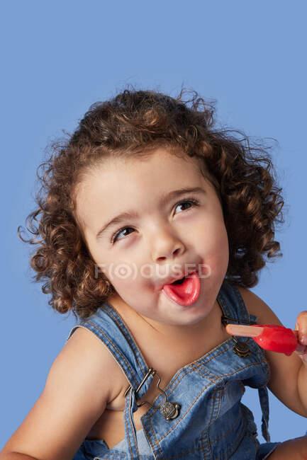 Забавная девушка в джинсовой одежде с вьющимися волосами, показывающими язык во время поедания сладкого мороженого на синем фоне — стоковое фото