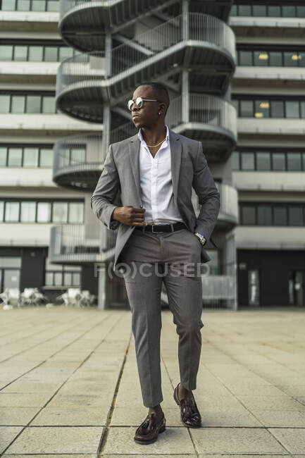 From below of adult well dressed black male executive in sunglasses looking away against multistory house in city — Stock Photo