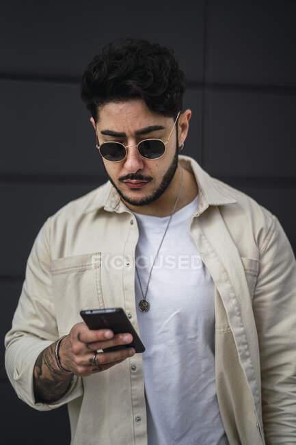 Сосредоточенный бородатый этнический мужчина в аксессуарах и модной одежде серфинг интернет на мобильном телефоне на улице в дневное время — стоковое фото
