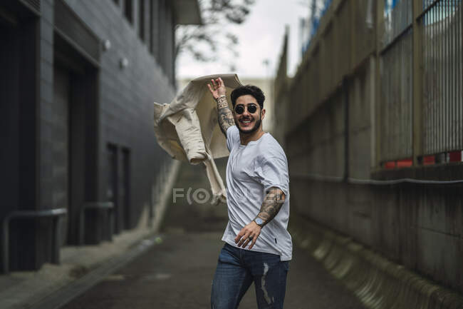 Young glad tattooed ethnic male in sunglasses and ripped jeans strolling on walkway between urban buildings — Stock Photo