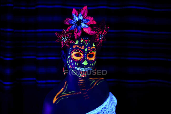 Anonymous female in multicolored masquerade mask with flowers on head looking at camera on Halloween night — Stock Photo