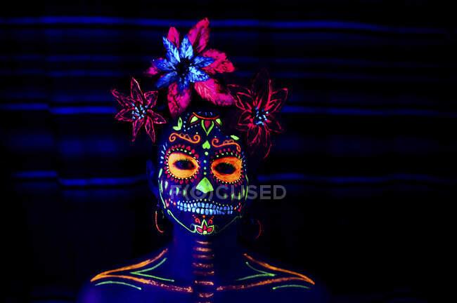 Анонімні жінки в різнокольоровій масці з квітами на голові, які дивляться на камеру вночі в Галовін. — стокове фото