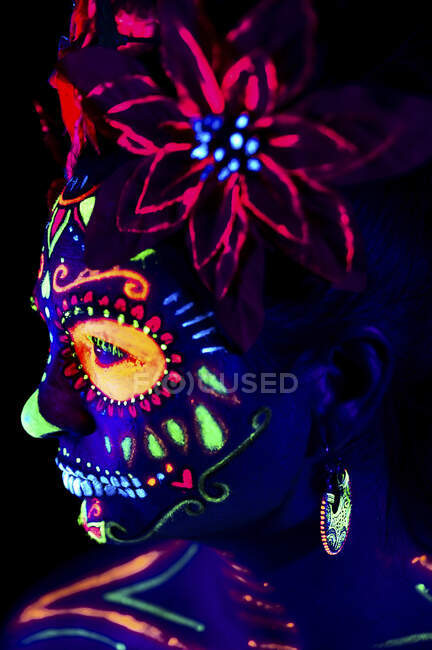 Anonymous female in multicolored masquerade mask with flowers on head looking away on Halloween night — Stock Photo