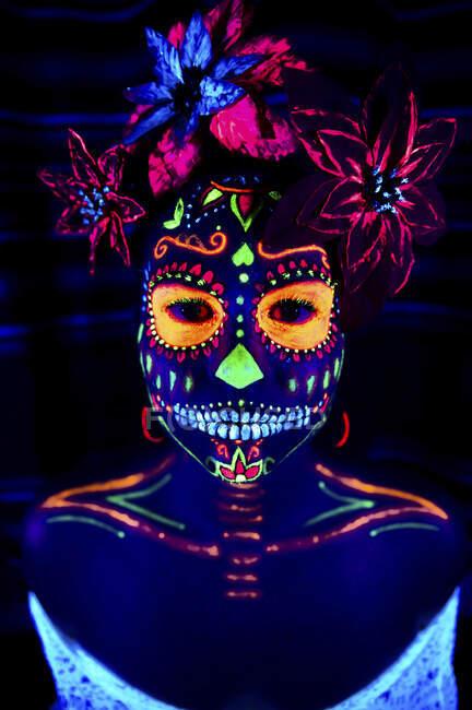 Anonymes Weibchen in bunter Maskerade mit Blumen auf dem Kopf blickt in der Halloween-Nacht in die Kamera — Stockfoto