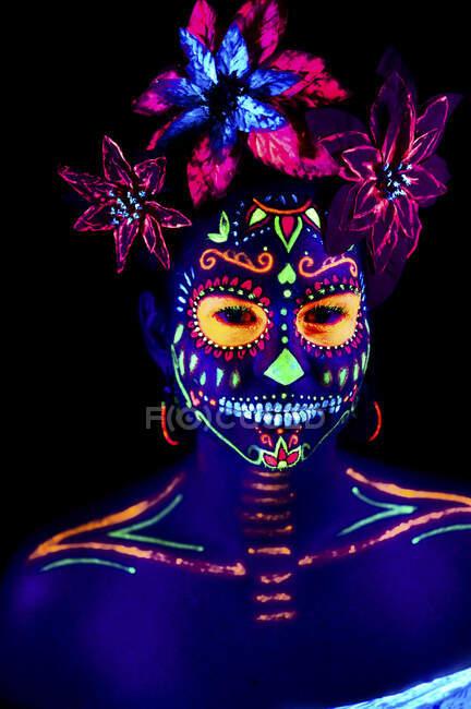 Mulher anônima em máscara de máscaras multicoloridas com flores na cabeça olhando para a câmera na noite de Halloween — Fotografia de Stock
