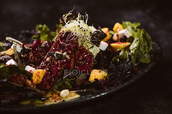 Plato con sabrosa ensalada vegetariana indonesia con mango fresco y rodajas de queso anacardo cerca de soja y condimentos cubiertos con vinagreta de albahaca - foto de stock