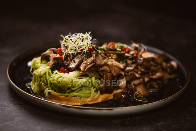 Yummy vegan dish with zucchini spaghetti and sauteed mushroom slices covered with red berries and alfalfa sprouts on dark background — Stock Photo