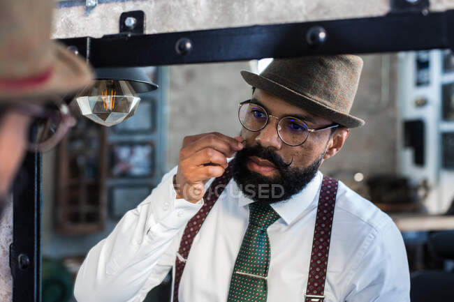 Crop bearded dandy ethnic male hairdresser in eyeglasses reflecting in mirror while curling mustache in barbershop — Stock Photo