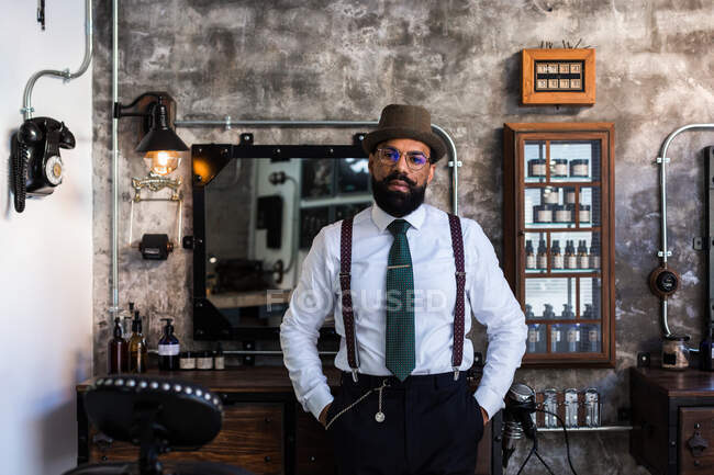 Confident ethnic bearded barber wearing classy outfit standing with hands in pockets in modern barbershop and looking at camera — Stock Photo