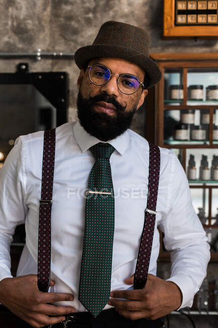 Crop bearded dandy ethnic male hairdresser in eyeglasses with mustache standing looking at camera in barbershop — стоковое фото