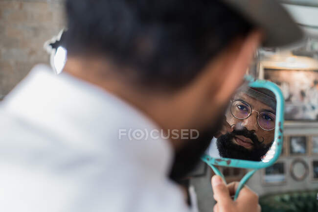 Back view of crop bearded dandy ethnic male hairdresser in eyeglasses reflecting in mirror while curling mustache in barbershop — Stock Photo