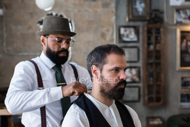 Middle aged ethnic male beauty master touching shirt of masculine client with beard in hairdressing salon — Stock Photo