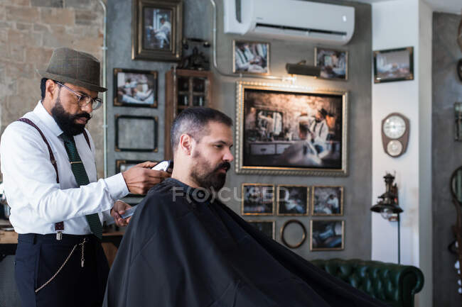 Side view of stylish dandy serious ethnic male barber trimming hair of adult client with electric clipper in hairdressing salon — Foto stock