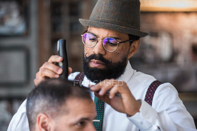 Stylish dandy serious ethnic male barber trimming hair of adult client with electric clipper in hairdressing salon — Fotografia de Stock