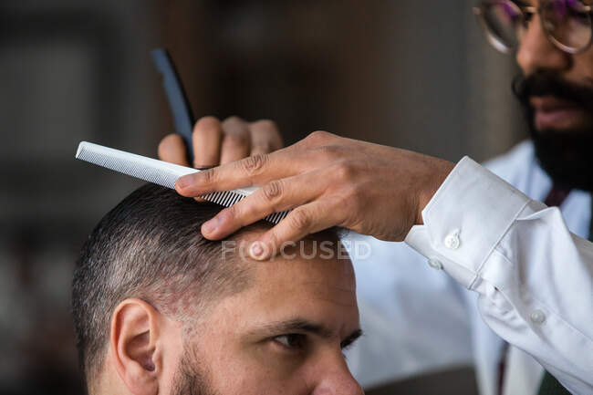 Crop stylish ethnic male beauty master removing hair of masculine client using straight razor in hairdressing salon — Stock Photo