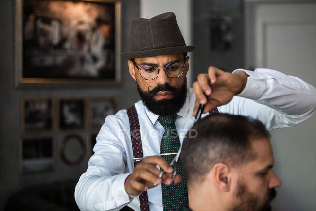Serious mature bearded ethnic male barber trimming hair of client with scissors during grooming procedure in beauty salon — Stock Photo