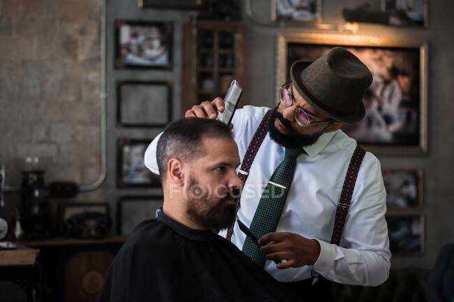 Stylish dandy serious ethnic male barber trimming hair of adult client with electric clipper in hairdressing salon — Stock Photo