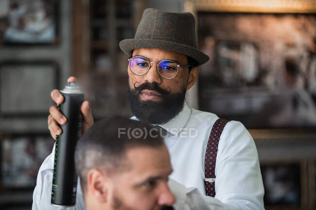 Mature ethnic male barber in formal clothes applying spray on haircut of crop man during beauty procedure in hairdressing salon — Stock Photo